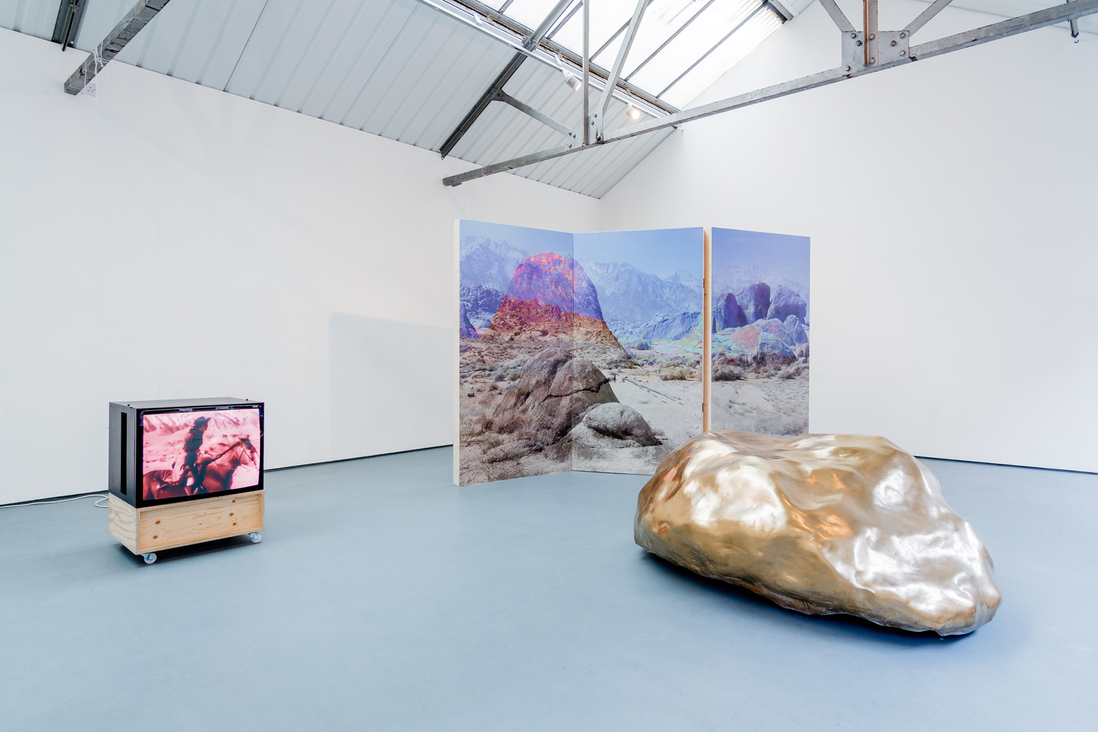 Lay of the land (and other such myths) | Victoria Lucas | 2016-17 | found video footage, digital photograph on mdf screen, plaster gold boulder | installation view: Bloc Projects, Sheffield | image: Jules Lister Photography